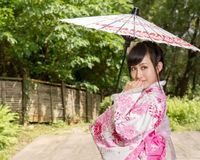 Asian woman wearing a kimono sitting in Japanese garden Royalty Free Stock Photos