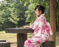 Asian woman wearing a kimono at a table in Japanese garden Stock Photography