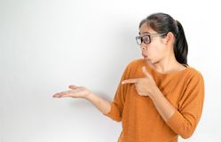 Asian woman wearing orange shirt and eyeglasses holding copy space on the palm and pointing on it while have shocked face. stock image
