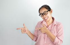Asian woman wearing pink shirt and eyeglasses  on white background smiling and looking at the camera pointing with two. Asian woman wearing pink shirt and stock photo