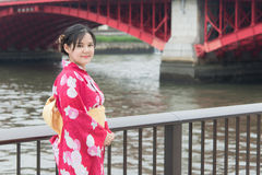 Asian woman wearing red kimono walking on a bridge Stock Photo