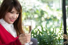 Woman wearing red sweater holding wine glass for birthday or ann Royalty Free Stock Photography