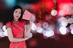 Asian woman wearing red traditional dress holding red pocket with the chinese new year festival background with lanterns stock image