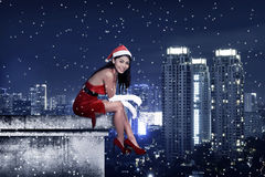 Asian woman wearing santa claus costume sit on the rooftop. Christmas present Stock Image