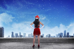 Asian woman wearing santa claus costume, standing on the rooftop. Looking the city Stock Image