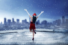 Asian woman wearing santa claus costume, standing on the rooftop. Looking the city Royalty Free Stock Photography