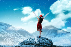 Asian woman wearing santa claus costume standing on the top of mountain Stock Photo