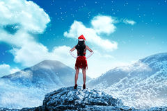 Asian woman wearing santa claus costume standing on the top of mountain Royalty Free Stock Photography