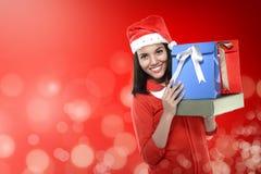 Asian woman wearing santa hat holding gift Stock Photos