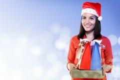 Asian woman wearing santa hat holding gift Stock Image