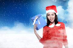 Asian woman wearing santa hat holding gift Stock Images