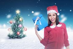Asian woman wearing santa hat holding present. With christmas tree background Stock Image