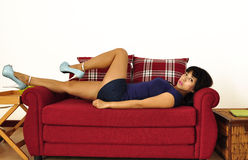 Asian woman wearing short blue dress lies on red sofa Stock Images
