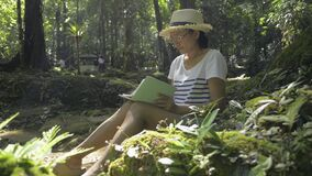 Asian woman wearing straw hat sitting and writing on a notebook under a tree. Biologist taking note about natural data.