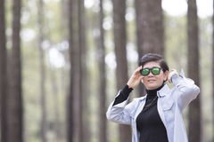 Asian woman wearing sun glasses standing in pine wood forest rel Stock Image
