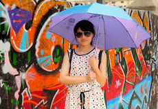 An Asian woman. Wearing sunglasses and holding an umbrella against a graffiti colored wall in M50 area on Moganshan road in Shanghai China royalty free stock photos