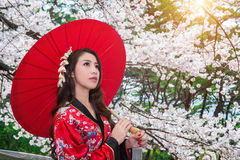 Asian woman wearing traditional japanese kimono with red umbrella. Stock Photo