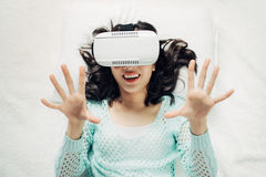 Asian woman wearing vr goggles lying on bed. Asian woman wearing vr goggles lying on bed Stock Photos