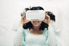 Asian woman wearing vr goggles lying on bed. Asian woman wearing vr goggles lying on bed Stock Photography
