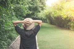 Asian woman wearing weave hat and walking on footpath in outdoor garden with green natural and sunlight background. Relaxation Concept : Asian woman wearing Stock Image