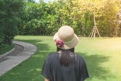 Asian woman wearing weave hat and walking on footpath in outdoor garden with green natural and sunlight background. Relaxation Concept : Asian woman wearing Royalty Free Stock Photo