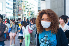 Asian woman is wearing white protective mask in the crowd of people. Tokyo city, Japan Stock Photos