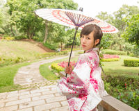Asian woman wearing a yukata and holding an umbrella in Japanese Royalty Free Stock Image
