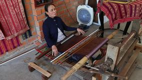 Asian woman weaves a national pattern on a machine. Nha Trang, Vietnam - 03 March, 2017. Ethnic women hand weaver. Asian woman weaves a national pattern on a stock video footage