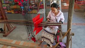 Asian woman weaves a national pattern on a machine.