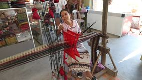 Asian woman weaves a national pattern on a machine. Nha Trang, Vietnam - 03 March, 2017. Weaver in China. Asian woman weaves a national pattern on a machine stock video footage