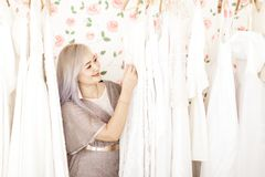 Weddign dress shop owner. Asian woman wedding dress shop owner take care for her products royalty free stock photos