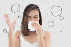 Asian woman in white dress catch her nose because of a bad smell. Against gray background royalty free stock photos