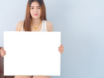 Asian woman in white vest holding White board . Stock Images