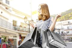 Asian Woman With Sunglasses Carrying Black Shopping Bags In The City Stock Image