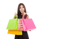 Asian woman wonder point to empty space with shopping bags. Isolated on white background stock photo
