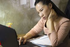 Asian woman worker suffering from hurt,fatigue, pain at neck, muscle, stressed during working with laptop for a long time, Office stock image