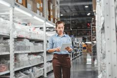 Asian woman worker working with digital tablet checking boxes Logistic import and export supplies packages in Warehouse , royalty free stock images