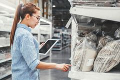 Asian woman worker working with digital tablet checking boxes Logistic import and export supplies packages in Warehouse , royalty free stock photography