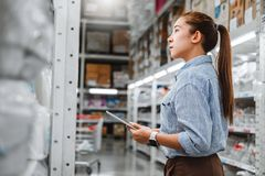 Asian woman worker working with digital tablet checking boxes Logistic import and export supplies packages in Warehouse , stock image