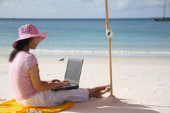 Asian Woman working on the beach. Asian woman with pink hat working on the beach in Queensland, Australia Royalty Free Stock Image