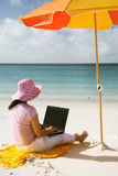 Asian Woman working on the beach. Asian woman with pink hat working on the beach in Queensland, Australia Stock Photo