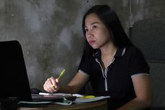Asian woman working from home late at night Work in poor lighting concept. dark light have some grain and noise royalty free stock photo