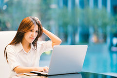 Asian woman working with laptop at home or modern office. Serious, confused, or frustrated expression. With copy space stock photo