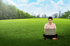 Asian woman working with laptop and sitting on the grass Stock Images
