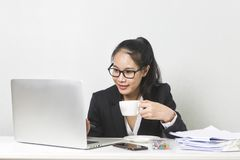 Asian woman working with laptop at white working table, diligent professional working woman drinking coffee while working on lapto. Happy business Asian woman stock photo