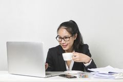 Asian woman working with laptop at white working table, diligent professional working woman drinking coffee while working on lapto. Happy business Asian woman royalty free stock photography