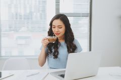 Asian woman working at office drinking coffee smiling at desk.  Stock Photography