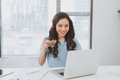 Asian woman working at office drinking coffee smiling at desk.  Stock Photos