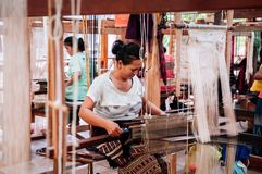 Asian Woman working on Vintage Laos style wooden weaving loom with silk fiber. APR 4, 2018 Luang Prabang, Laos - Laotian woman working on Vintage Laos style stock photography