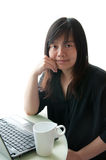 An asian woman works with computer and coffee cup Royalty Free Stock Image